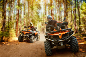 Two atv riders, speed race in forest, front view. Fourwheeler accidents concept..