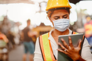 Workers comp concept. African American black women teen worker wearing face shield or disposable face mask during working in factory for prevent spreading of Coronavirus(Covid-19) and air dust pollution for labor healthy.
