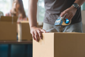 missouri relocation law concept young couple moving house. Close-up hand of man use tape sealing cardboard box.